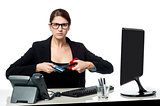 Serious faced woman cutting her credit card