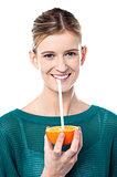Girl sipping orange juice through straw