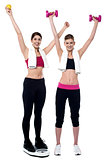 Two smiling girls working out together