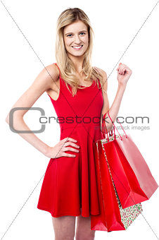 Attractive girl holding vibrant shopping bags