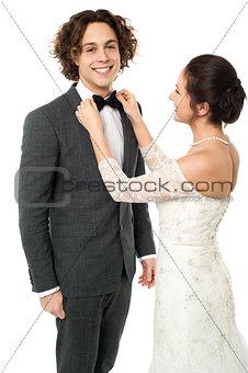 Bride adjusting her man's bow tie
