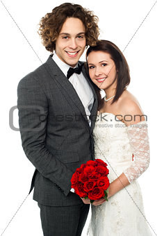 Affectionate wedding couple posing together