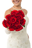 Smiling young bride holding out a rose bouquet