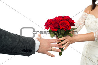 Bride offering rose bouquet to the groom