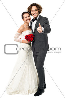 Groom with his bride showing thumbs up sign