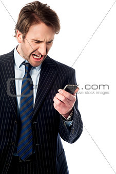 Angry businessman looking at his phone