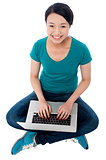 Cheerful attractive girl working on laptop