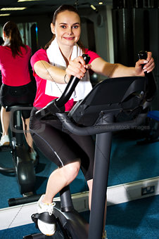 Athletic woman cycling at the gym