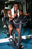 Muscular man on excercise bike at the gym