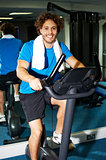 Fitness man riding a static bike inside gym