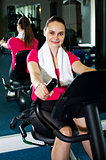 Cheerful woman doing cycling at fitness centre