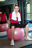 Pretty fit woman sitting on pink swiss ball