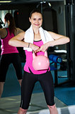 Smiling fit woman lifting kettlebell
