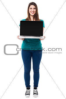 Casual girl presenting brand new laptop