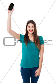 Beautiful young woman holding up a cell phone