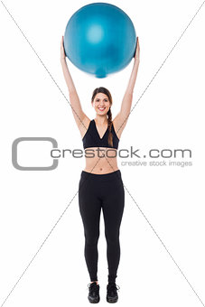 Fitness enthusiast holding ball above her head