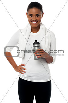 Fitness freak holding sipper, towel around her neck