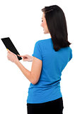 Smiling attractive girl operating touch pad device