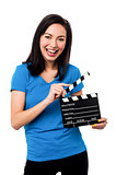 Young girl holding clapperboard