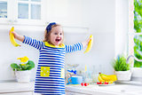 Little girl preparing breakfast in a white kitchen