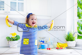 Little girl preparing breakfast in a white kitchen
