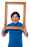 Excited young male holding wooden frame