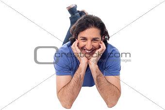 Casual young man lying on the studio floor