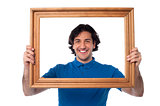 Smiling guy looking through picture frame