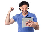 Excited young man holding touch pad device