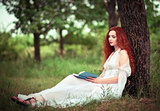 Cute red-haired woman sitting under tree and reading a book