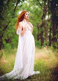 Beautiful ginger woman wearing white dress in a garden