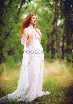 Beautiful ginger woman wearing white dress in a garden