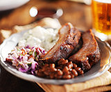 barbecued spare rib meal with beer and fixings like baked beans, cole slaw, and potato salad