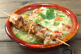 Chicken soup with chicken skewers and noodles