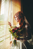 Beautiful red hair bride near window