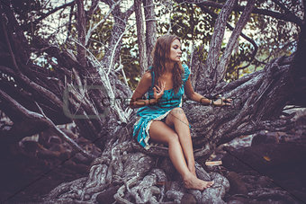 Portrait of beautiful elegant lady  with dress in a green jungle rainforest. Retro colors