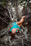 Beautiful young woman in a turquoise dress lying on roots of tree In the rainforest