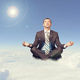Businessman sitting in lotus position on cloud