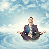Businessman sitting in lotus position on circles