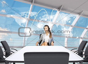 Businesslady sitting at table with world map