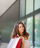 Smiling woman shopping, holding up colourful shopping bags