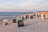 Beach chairs with dunes at sunset