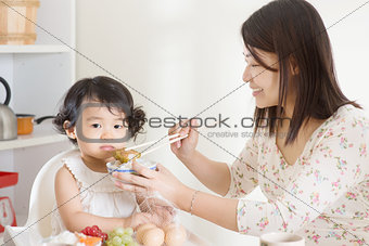 Asian mother feeding child