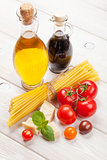 Pasta, tomatoes, basil on wooden table