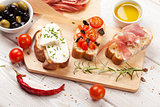 Bruschetta with cheese, tomatoes and prosciutto