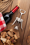 Red wine bottle, bowl with corks and corkscrew