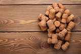 Heap of champagne corks over rustic wooden table background