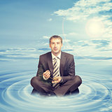 Businessman sitting on cloud with oil lamp
