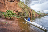 canoe paddler and sandstone cliff