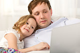 Father and little daughter using laptop